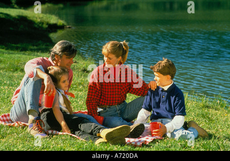 Famille d'un père mère fils fille et un pique-nique tout en étant assis sur une couverture près d'un lac Banque D'Images