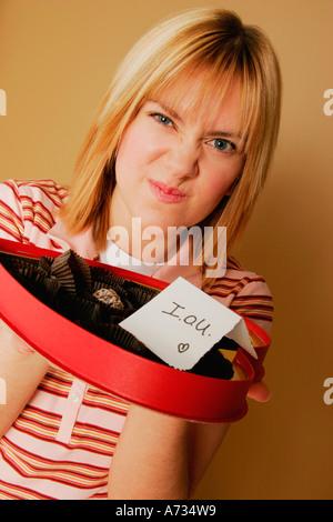 Une adolescente bouleversé par une boîte vide de chocolats Banque D'Images