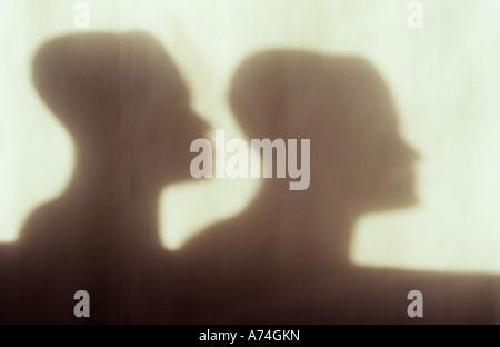 Dans l'Ombre lumière chaude sur chiffon pâle ou le rideau de deux modèles de têtes dans un profil adultes derrière Banque D'Images