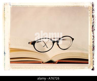 Les lunettes assis sur un livre ouvert Banque D'Images
