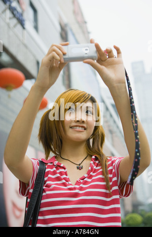 Teenage girl taking photo with cell phone