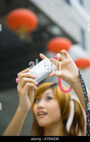 Teenage girl taking photo with cell phone Banque D'Images
