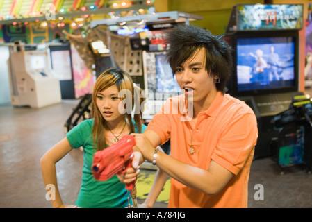 Jeu de couple dans une salle de jeux vidéo Banque D'Images