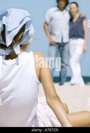 Girl sitting on beach, face parents en arrière-plan, vue arrière Banque D'Images