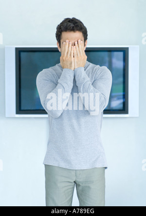 Homme debout en face d'une télévision grand écran, mains covering face Banque D'Images