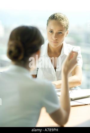 Deux jeunes femmes assis l'un en face de l'autre, avoir une conversation, se concentrer sur la femme à l'écoute Banque D'Images
