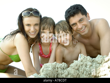 Family playing in sand at beach, smiling at camera, portrait Banque D'Images