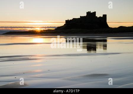 L'esquisse de Château de Bamburgh reflétée dans le sable humide de la plage Banque D'Images