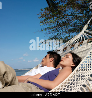 Couple in hammock on beach Banque D'Images