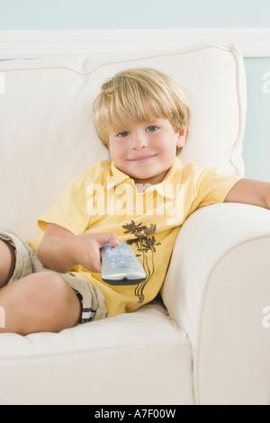 Jeune garçon sur canapé pointant télécommande Banque D'Images