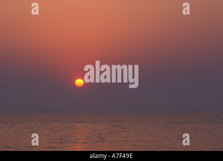Une vague de sérénité avec coucher de soleil rougeoyant au-dessus d'une vaste étendue d'eau libre de disparaître Banque D'Images