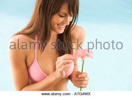 Une jeune femme dans un bikini tient une fleur Banque D'Images