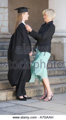 Une mère contrôle ses études supérieures la robe de fille Banque D'Images