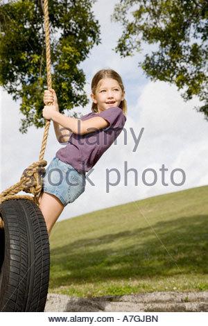 Une jeune fille jouant sur une balançoire Banque D'Images