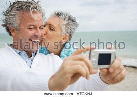 Un couple sur une plage de prendre une photo avec un appareil photo numérique Banque D'Images