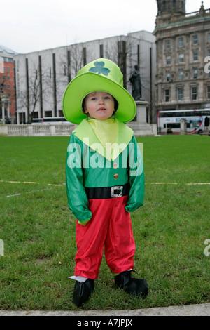 Jeune garçon habillé comme un lutin debout sur l'herbe dans le parc de Belfast City Hall sur St Patricks Day 2007 Banque D'Images
