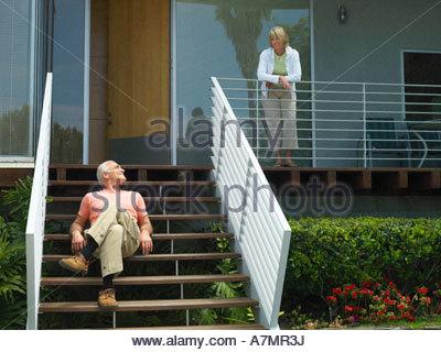 Senior couple relaxing at home femme debout sur l'homme assis sur une véranda comme suit smiling Banque D'Images