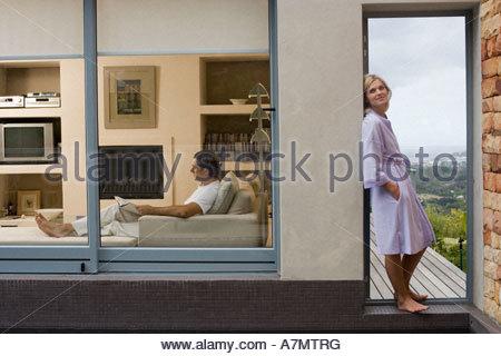 Couple relaxing at home homme sur canapé femme debout sur balcon vue latérale leaning against wall Banque D'Images