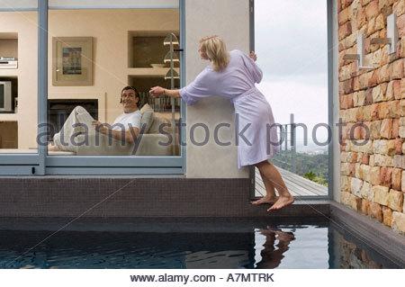 Couple relaxing at home homme sur canapé femme debout sur balcon fenêtre frappant Banque D'Images