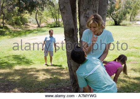 Famille joue à cache-cache dans le parc de la mère et des enfants 811 se cacher derrière le père de l'arbre à Banque D'Images