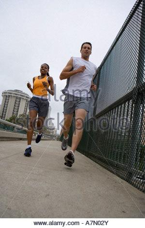 USA California San Diego couple jogging le long de l'inclinaison au niveau de la surface de passage Banque D'Images