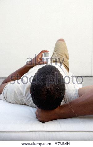 Détente à la maison de l'homme allongé sur le dos listening to MP3 player vue arrière Banque D'Images