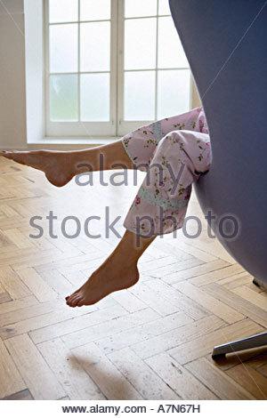 Femme en pyjama assis dans un fauteuil à la maison les pieds Vue de côté la section basse Banque D'Images
