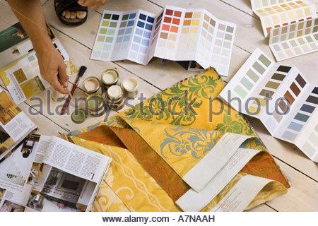 L'homme à la maison de décoration de pots de peinture à côté d'échantillons de couleur et les magazines de bricolage Banque D'Images