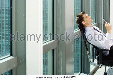 Businessman sitting in chair à côté de la fenêtre du bureau en se penchant en arrière penser smiling side view Banque D'Images