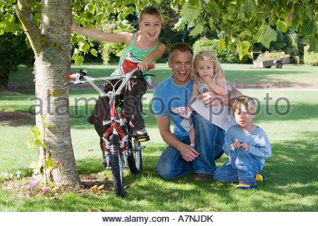 Père de trois enfants 39 à genoux sur l'herbe à côté de tree in garden girl sitting on bike smiling portrait vue Banque D'Images
