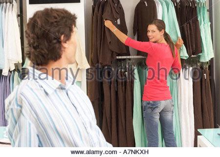 L'homme à la petite amie de choisir à partir de rail en magasin de vêtements smiling accent sur l'arrière-plan Banque D'Images