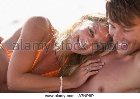 Young couple relaxing on beach rire blond woman wearing bikini orange portrait Banque D'Images