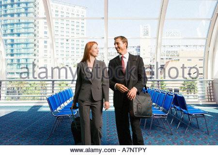 Businessman and woman walking with luggage en remorque dans la salle d'embarquement de l'aéroport Vue de face souriante Banque D'Images