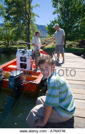 Boy 810 assis sur la jetée du lac smiling side view portrait grand-père et le chargement des cannes à pêche en bateau Banque D'Images