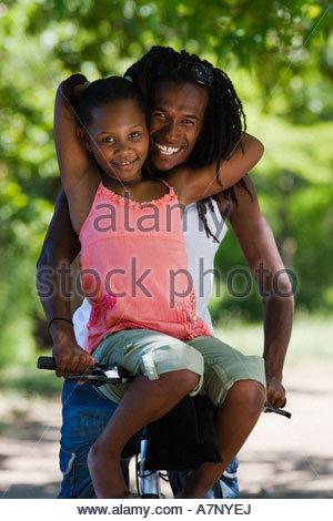 Père et fille 79 assis sur vtt girl resting sur guidon smiling portrait Banque D'Images