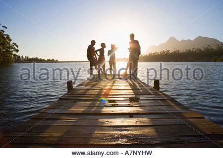 Famille dans le bain debout à bord de la jetée du lac au coucher du soleil photo Banque D'Images