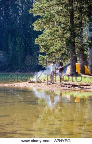 Couple dans la mi distance pêcher près de Camp au bord du lac woman holding en altitude, vue latérale du poisson Banque D'Images