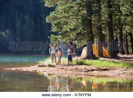 En famille au bord du lac de pêche à moyenne distance on camping trip woman holding attraper l'homme avec la canne Banque D'Images