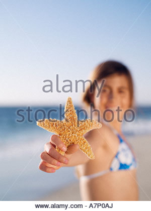 Girl 1012 brandissant starfish on sandy beach smiling portrait focus on foreground Banque D'Images