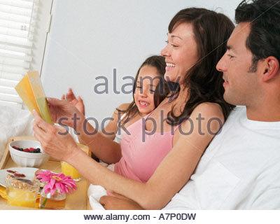 Femme assise au lit à la maison, l'ouverture de la fête des mères, carte fille (5-7) et mari à la vue de côté, sur Banque D'Images