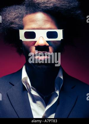 Homme Afro Antillais portant des lunettes 3D à l'arrière-plan rouge Banque D'Images