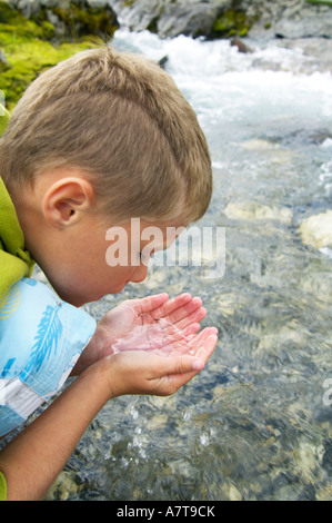 Close-up of boy drinking water from river Banque D'Images