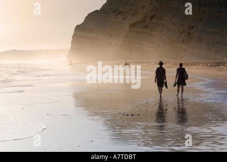 Silhouette de touristes marcher sur la plage Praia De Porto De Mos Algarve Portugal Banque D'Images