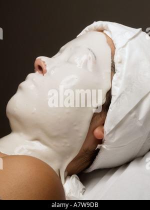 Femme portant un masque de visage liquide en caoutchouc au cours d'un salon de beauté traitement de la peau Banque D'Images