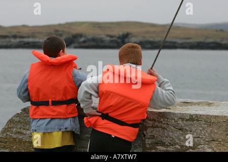 Deux jeunes garçons adolescents portant des gilets haute visibilité orange en attente d'un bateau pour venir sur Banque D'Images