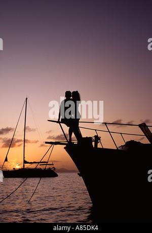 BVI Cooper Island sur couple romantique au coucher du soleil de chalutiers bow Banque D'Images
