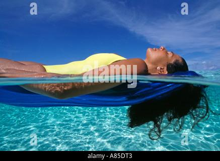 Banc de Grand Cayman en vertu d'une femme en costume jaune flotte dans l'eau peu profonde claire Banque D'Images