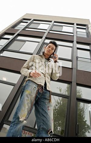 Un jeune homme à l'aide de téléphone mobile, low angle view Banque D'Images