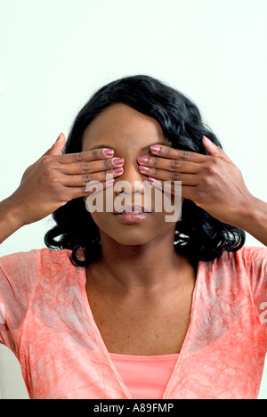 Une jolie jeune femme noire ethnique couvrant ses yeux avec ses mains Banque D'Images