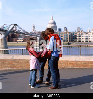 Une famille sur une journée en regardant une carte par le Millennium Bridge, South Bank, Londres Angleterre Royaume Banque D'Images